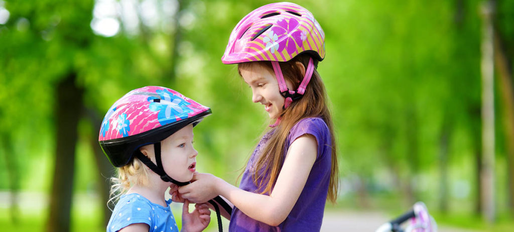 Photo of older kid buckling younger kid's helmet.