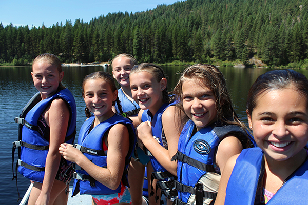 Photo of girls in life jackets on lake.