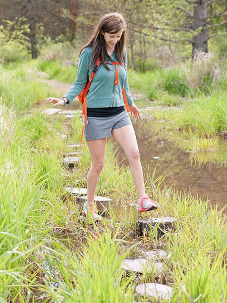Photo of girl walking across tree stumps.