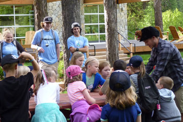 Camp Spalding summer staff teaching campers about wildlife as they touch animal pelts before going on a hike.