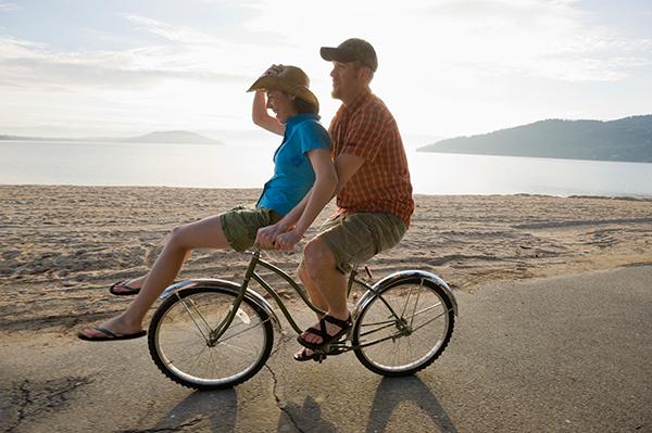 Photo of couple riding a bike along the beach.