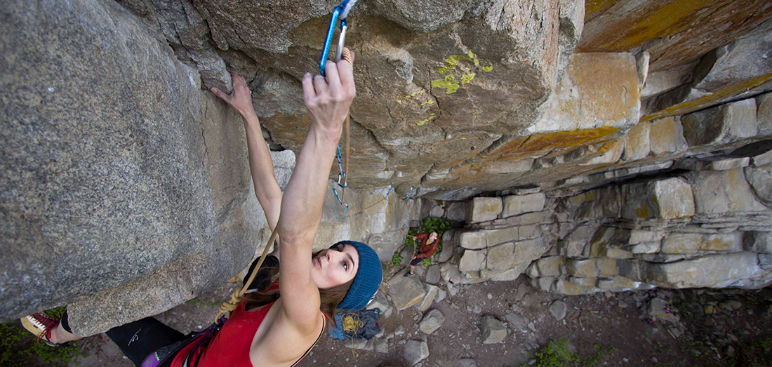 Photo of climber clipping on a lead route in Pack Rat Cave.