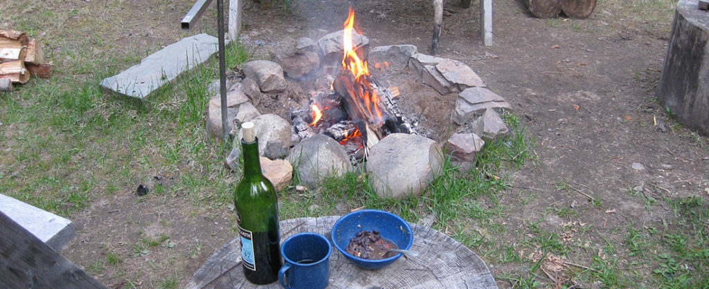 Photo of campfire with bottle of wine, coffee cup, and bowl resting on a tree stump.
