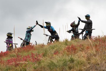 Photo of mountain bikers high-fiving underneath the gondola.