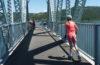 Photo of kids rollerblading across bridge.