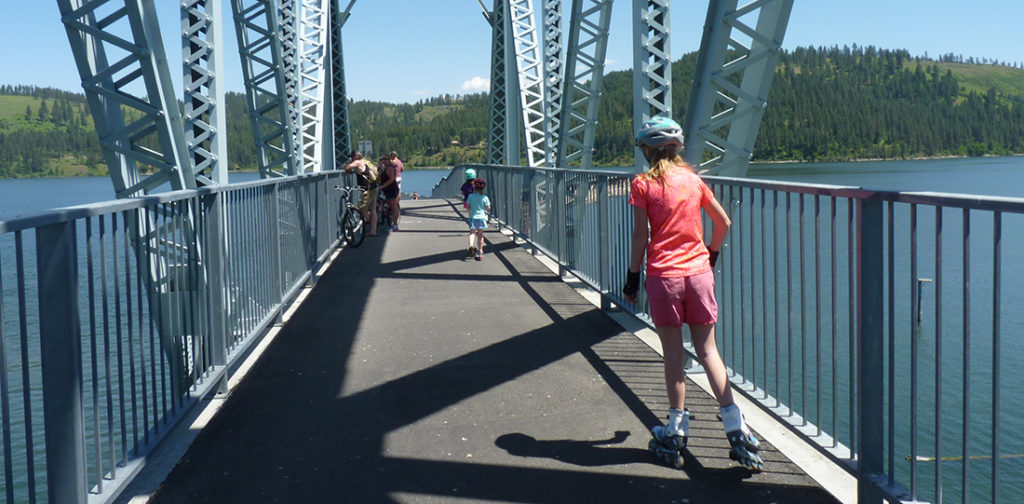 Photo of kids rollerblading across bridge.