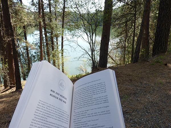 Photo of open book and lake in the background.
