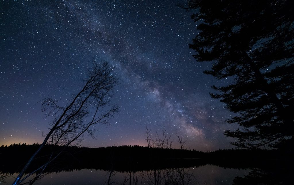 Photo of a lake with stars above.