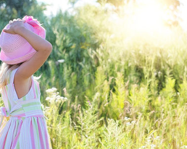 Little girl in sundress and hat in field.