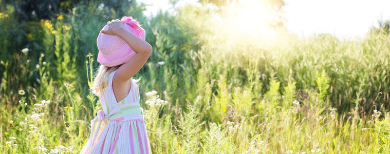 Little girl in sundress and hat in field.