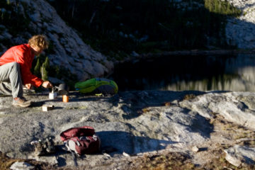 An adult woman lying on a camp pad journaling and an adult man boiling water during a backcountry camping trip in the Selkirk Mountains of Northern Idaho.