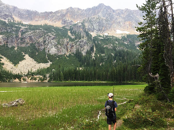 Photo of young boy hiking with alpine lake and mountains in the background.