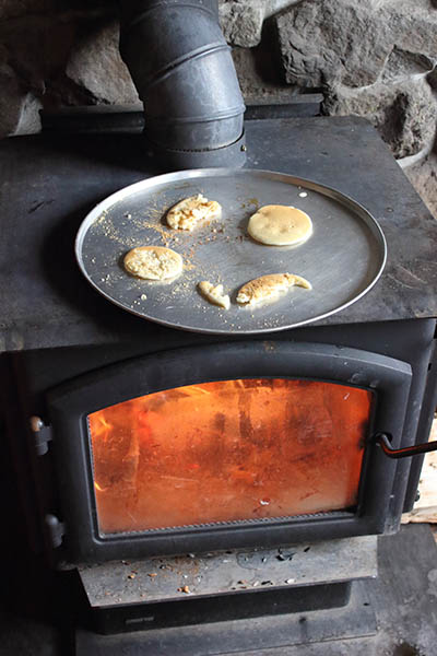 Photos of pancakes in skillet on top of wood burning stove.