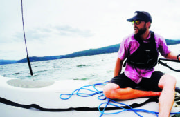 Photo of Jacob Rothrock reclining on a sailcraft on Lake Coeur d'Alene.