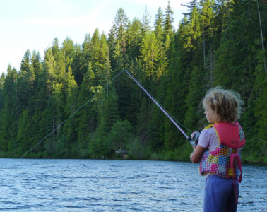 Photo of girl fishing in lake while standing on a log.