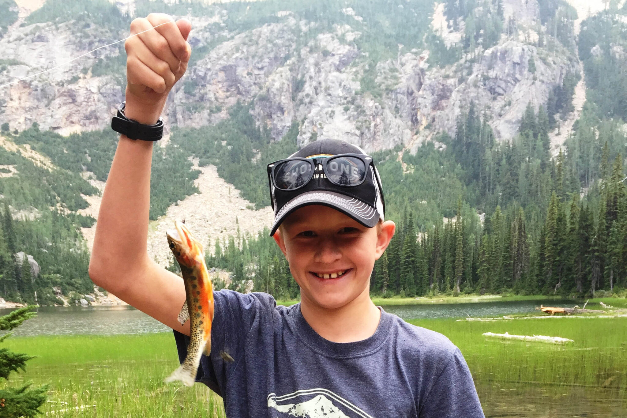 Photo of young boy holding a fish.