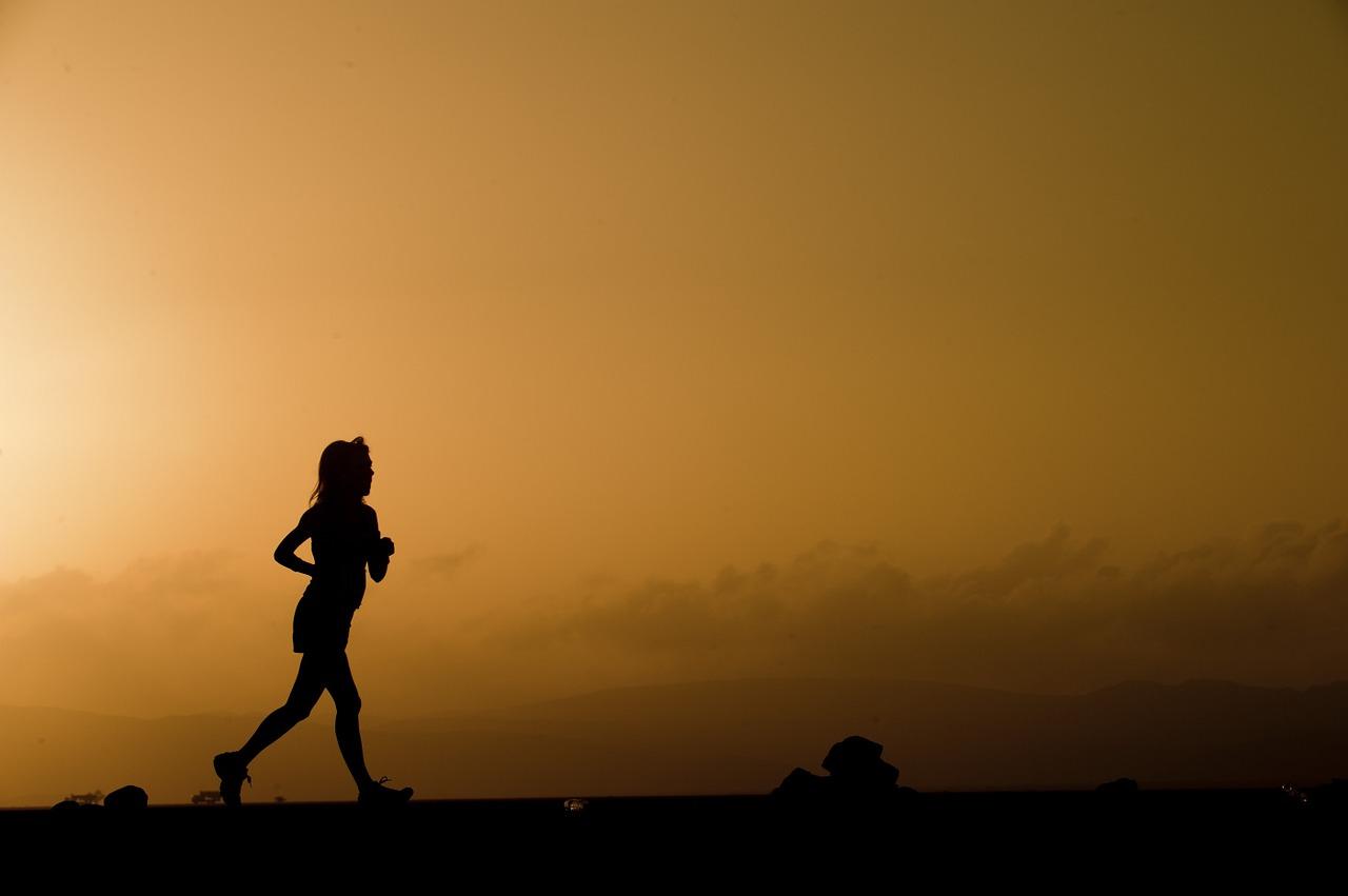 Silhouette of runner against orange sunset.