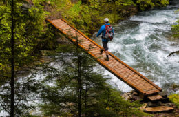 Hiker crossing wooden bridge over whitewater.