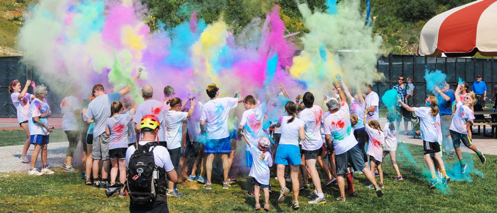 Photo of the Hukleberry Fun Run participants grouped around an explosion of colored powder.