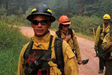 Photo of firefighters walking on dirt path in front of a fire.