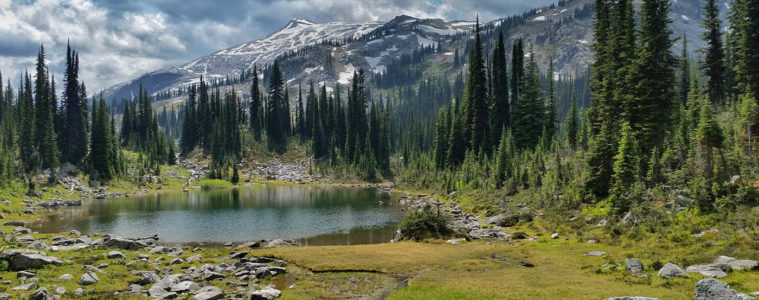 Photo of alpine lake with mountain peak in the background.
