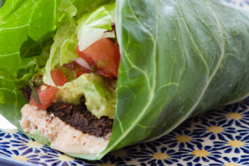Photo of lettuce wrap with meat, guacamole, and vegetables.