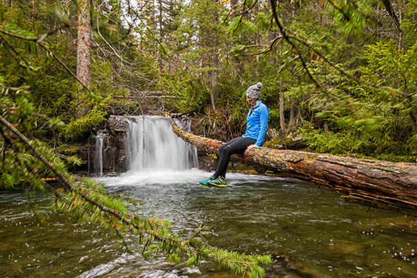 Photo of hiker sitting on log overhanging pool of water at base of a small waterfall.