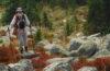Photo of hiker climbing steep boulder field.