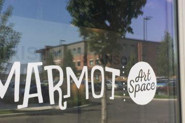 Photo of Marmot vinyl decal on door of gallery.