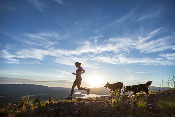An Adult Woman Running With Two Dogs On Top Of A Mountain Overlooking The Pend Oreille River In Sandpoint, Idaho