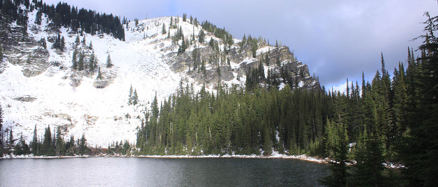 Photo of Lower Blossom lake with snow covered mountains in the background.