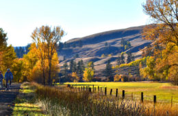 Photo of bikers along the Ferry County Rail Trail with fall colors.