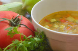 Photo of vegetable soup in bowl next to tomato and parsley.