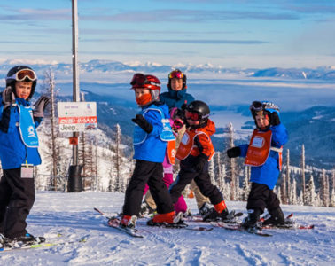 Photos of kids in a group ski lesson standing in front of a marked trail.
