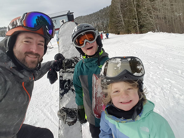 Selfie of Jason Graham with snowboard and two kids.