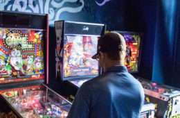 Photo of a man playing a Pinball arcade game at Berserk.