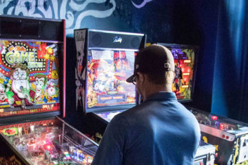 Photo of a man playing a Pinball arcade game at Berserk.