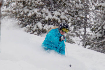 Photo of Kelli Christopherson skiing powder at Lookout Pass.