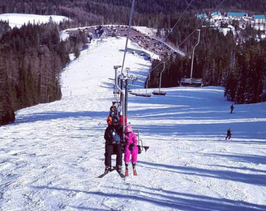 Photo taken from afar of father and daughter riding the chairlift at Mount Spokane.