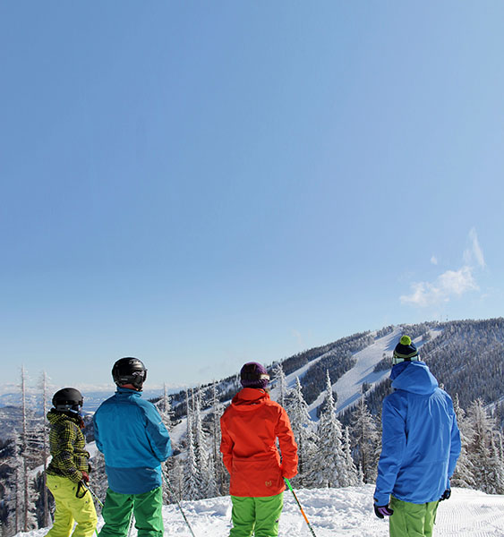 Photo of four skiers wearing brightly colored ski jackets taken from behind.
