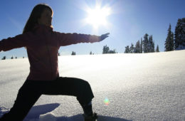 Photo of woman in yoga pose standing in untracked snow.