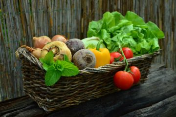Basil, peppers, tomatos, onions, and lettuce in a wicker basket.
