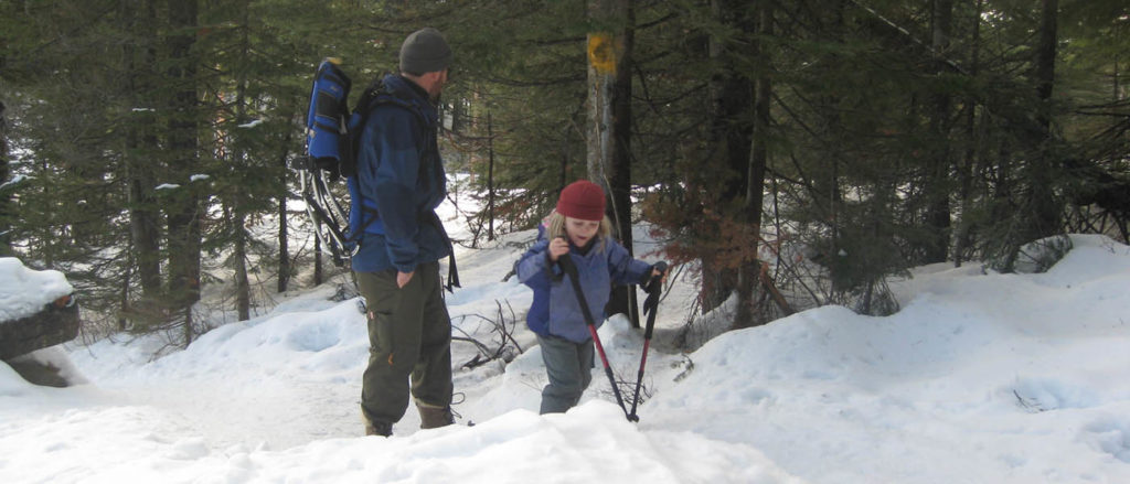 Photo of dad and son snowshoeing together.