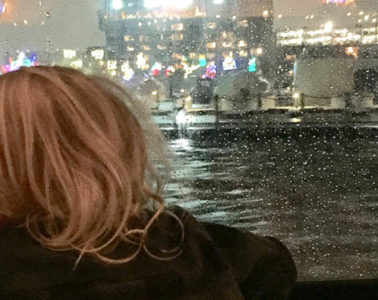 Photo of kid taken from behind looking out window at fireworks.