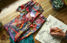 Photo of leggings on workbench along next to product sketch.