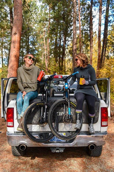 Photo of two girls and their bikes sitting on the back of pickup truck with the tailgate down.