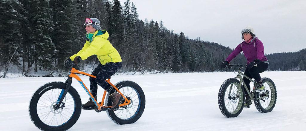 Photo of two girls fat biking on snow.