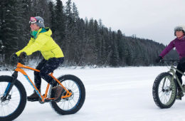 Photo of two girls fat biking on snow.
