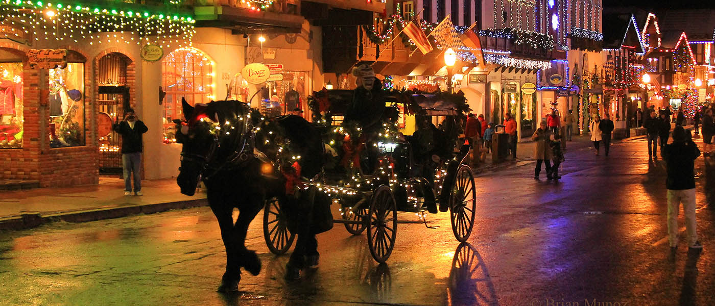 Photo of carriage down the main street of Leavenworth with lighted shops.