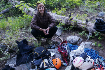 Photo of the author in front of a pile of climbing gear laid out on the ground.